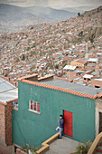 Local leans against house wall, view from El Alto to large urban area of La Paz, Andes, Bolivia, South America