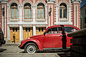 Uniformed general runs on street with red VW Beetle in front of colonial red house, old town of La Paz, Bolivia, Andes, South America