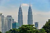 The Petronas Towers with skyscrapers and trees in Kuala Lumpur, Malaysia