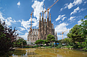 Gaudi Sagrada Familia Cathedral from outside with reflection in water at sun, Barcelona, Spain