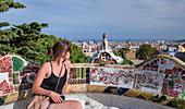 Frau auf Mosaikbank mit Ausblick auf die Stadt vom Park Guell in Barcelona\n