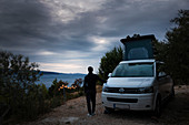 Man stands at campervan VW bus with sea view, dramatic clouds with dark mood lighting, Brac Croatia