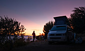 Woman stands at VW Campervan bus with sea view at sunset, Brac Croatia