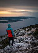 Man standing looking at Hvar island from Vidova Gora viewpoint on Brac at sunset, Croatia