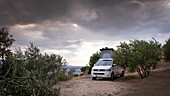Campervan VW bus between olive trees by the sea near Bol, dramatic clouds, Brac Croatia