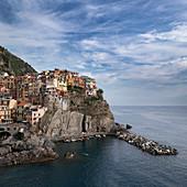 Bay in Cinque Terre with village Manarola in the afternoon, Italy
