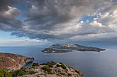 Lipari coastline with view of Vulcano volcanic island with dramatic clouds, Sicily Italy