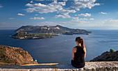 Lipari coast with woman sitting, looking at volcano island Vulcano at day, Sicily Italy