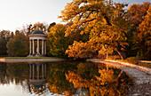 Apollo Tempel mit Baum im Schlosspark Nymphenburg im Herbst, am Wasser, München\n