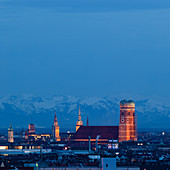 Munich city skyline with illuminated Frauenkirche and snowy Alps in the background at night