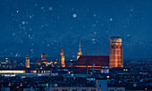 Munich city skyline with illuminated Frauenkirche during snowfall at night