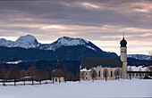 Pilgrimage church Wilparting am Irschenberg with snow in winter at sunrise, with mountains in the background, Bavaria