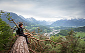 Woman sitting on tree trunk with a view of the valley on Berchtesgaden, Bavaria