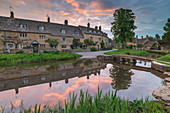 Colourful sunrise above the pretty village of Lower Slaughter in the Cotswolds, Gloucestershire, England, United Kingdom, Europe