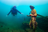 Scuba diver swimming by the submerged statue of Greek God Dionysus. Baia (Baiae), Campi Flegrei (Phlegraean Fields), Campania, Italy, Mediterranean, Europe