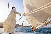 Ein ägyptischer Mann steht am Bug eines traditionellen Felucca-Segelboots mit Holzmasten und Baumwollsegeln auf dem Nil, Assuan, Ägypten, Nordafrika, Afrika
