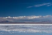 Die Schönheit der Salinen spiegelt die Wolken und Berge nach Regenfällen wider, drei Allradfahrzeuge in der Ferne, Uyuni, Bolivien, Südamerika