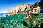 Women sunbathing with old boathouses in the back, Pollara, Salina, Aeolian Islands, UNESCO World Heritage Site, Sicily, Italy, Mediterranean, Europe