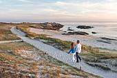 France, Morbihan, Quiberon, couple walk along the coastline at sunset
