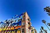 Palm trees and brightly painted facade of the Venice suites, Venice Beach, California, USA