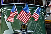 Classic car decorated with flags during a folk festival in Nevada City, California, USA