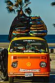 Old VW bus with surfboard rental on Santa Monica Beach, California, USA