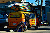 Surfboard owner sleeping in front of his old VW bus, Santa Monica, California, USA