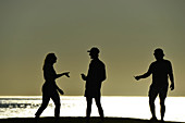Three young people as silhouettes in backlight on the Pacific Ocean, Santa Monica, California, USA