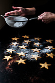 High angle close up of person dusting freshly baked star-shaped cookies with icing sugar.