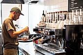 Bearded man wearing baseball cap standing at espresso machine a restaurant.