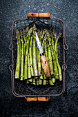 High angle close up of freshly picked green asparagus in metal basket.