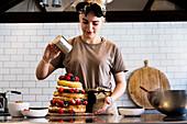 Köchin in einer gewerblichen Küche bestäubt einen geschichteten Biskuitkuchen mit frischem Obst und Sahne mit Puderzucker