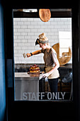 View through a door marked Staff Only, of a cook working in a commercial kitchen sprinking icing sugar over a layered cake with fresh fruit.