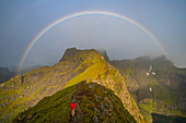 Man climbing towards a rainbow in the Lofoten Islands.
