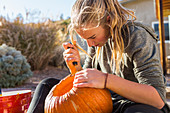 A teenage girl carving a pumpkin at Halloween,