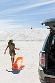 teenage girl with sled, White Sands Nat'l Monument, NM