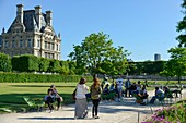 France, Paris, area listed as World Heritage by UNESCO, Garden of the Tuileries, walkers on a path in sand with the Museum dof Louvre in the background