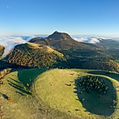France, Puy de Dome, area listed as World Heritage by UNESCO, Ceyssat, Chaine des Puys, Regional Natural Park of the Auvergne Volcanoes, summit of Puy de Come volcano and Puy de Dome in the background (aerial view)