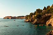 People kayaking in sea by rock formations, Dubrovnik, Croatia