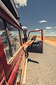 Feet hanging out of an off-road vehicle on a deserted road in the outback in Western Australia, Australia, Oceania;