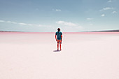 Male person stands on Pink Lake in Western Australia, Australia, oceans;
