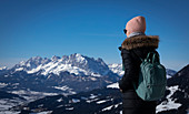 Woman with coat and cap looking at Ellmauer Halt in Fieberbrunn in the Wilder Kaiser near Winter, Tyrol