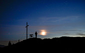 Person at the summit cross of the Jochberg at night with clouds, stars and moon
