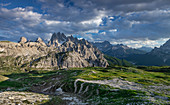 Mountain landscape below the Three Peaks in the Dolomites with sun and clouds, South Tyrol