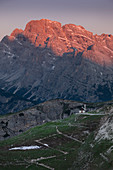 Sunrise over mountain landscape in the Dolomites below the Drei Zinnen with chapel and path, South Tyrol