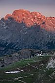 Sonnenaufgang über Berglandschaft in den Dolomiten unterhalb der Drei Zinnen mit Kapelle und Weg, Südtirol