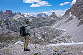 Man with a view to the Sasso di Sesto summit while hiking on the Three Peaks in the Dolomites Natural Park, South Tyrol