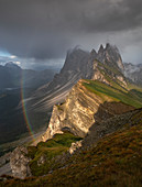Seceda mountainside with thick clouds, sun and rainbow in the Dolomites near Ortisei, South Tyrol