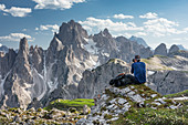Man photographs mountain landscape in the Dolomites below the Lavardo hut at the Drei Zinnen a day, South Tyrol