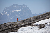 Woman hikes over rock edge, mountains of the Dolomites in the background, with snow field, Cinque Torri South Tyrol